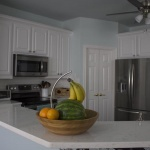 The beautiful, long, white quartz countertop stretches all around the kitchen.