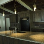 New granite countertops accentuate custom copper light fixtures above.