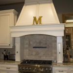 Here's a pretty thing — a marble tile backsplash! The oversized hood is seamlessly integrated with the rest of the room, and don't you just love the family's initial in gold on top?