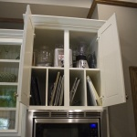 More storage! This cabinet just above the oven comes with built-in dividers for cutting boards and appliances alike.