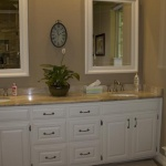 His & hers vanities with thick framed mirrors, stylish granite countertops, and white painted cabinets.